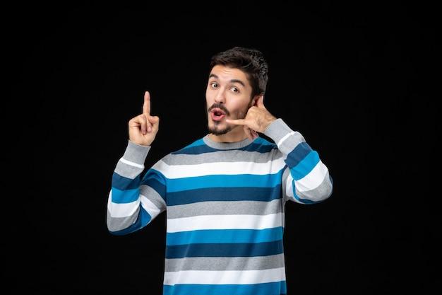 Giovane uomo in maglia a righe blu che fa il gesto del telefono con la mano e punta verso l'alto