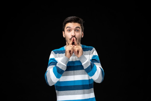 Young man in blue striped jersey doing silence gesture with fingers on lips