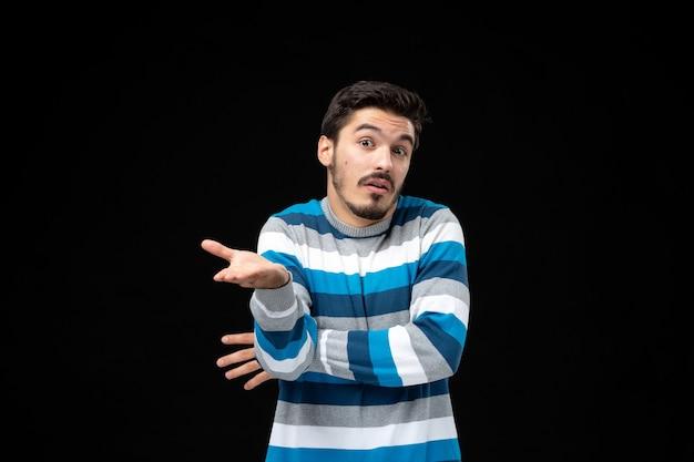 Giovane uomo in maglia a righe blu che parla con te