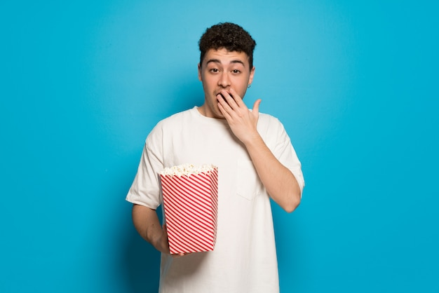 Young man over blue  surprised and eating popcorns