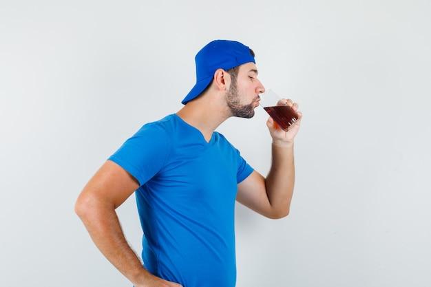 Giovane uomo in maglietta blu e berretto che beve bevanda fredda e sembra assetato