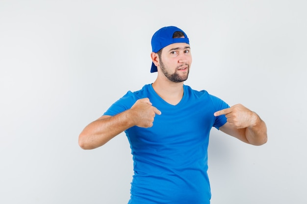 Young man in blue t-shirt and cap pointing at himself and looking proud