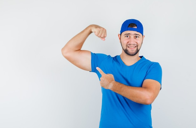 Young man in blue t-shirt and cap pointing at his muscles and looking confident