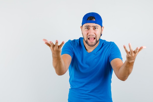 Young man in blue t-shirt and cap raising hands in questioning manner and looking aggressive