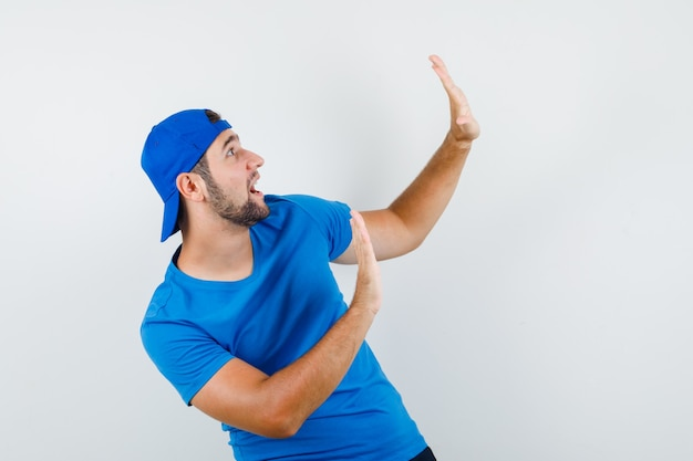 Young man in blue t-shirt and cap showing stop gesture and looking scared