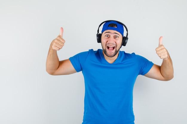 Giovane uomo in maglietta blu e cappuccio che indossa le cuffie mentre mostra i pollici in su e sembra felice