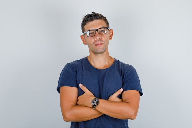 Young man in blue t-shirt, glasses folding hands on chest and looking serious, front view.