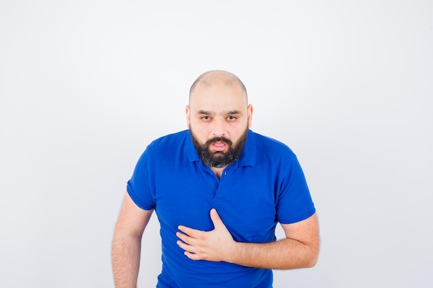 Young man in blue t-shirt having a stomachache