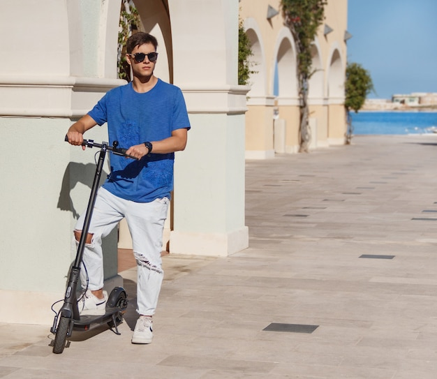 Young man in blue t-shirt stays with an electric scooter on the street near the sea