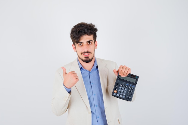 Giovane in maglietta blu e giacca bianca che tiene la calcolatrice e mostra il pollice in su e sembra amabile a