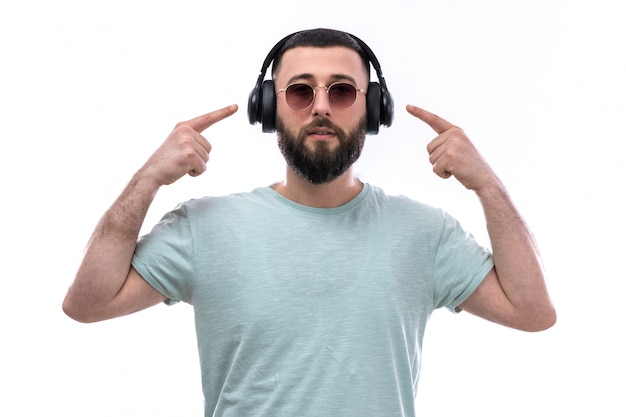 Young man in blue t-shirt with beard listening to music through black headphones