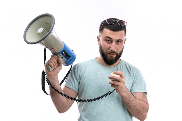 Young man in blue t-shirt with beard and sunglasses holding megaphone