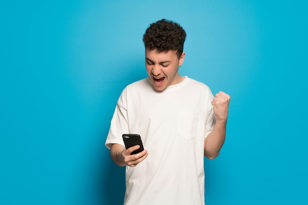 Young man over blue wall celebrating a victory with a mobile