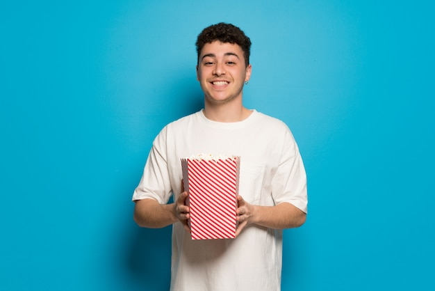 Young man over blue wall eating popcorns