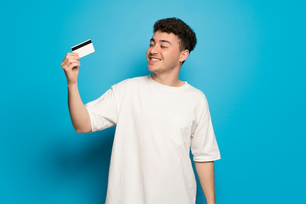 Young man over blue wall holding a credit card and thinking