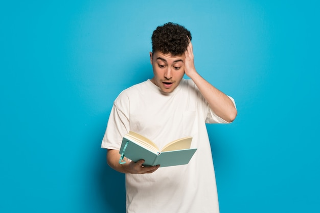 Young man over blue wall surprised while enjoying reading a book