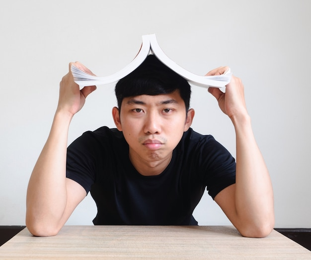 지루하고 낙담한 젊은이는 머리에 있는 책을 닫습니다.공부와 숙제 개념