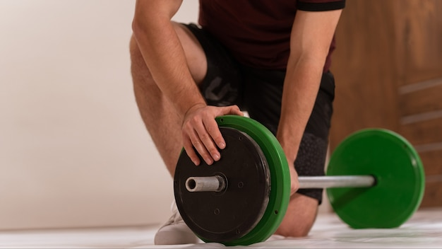Молодой человек кланяется на колено, готовит аксессуары для фитнеса в черно-зеленых тонах, оборудование для веса Premium Фотографии