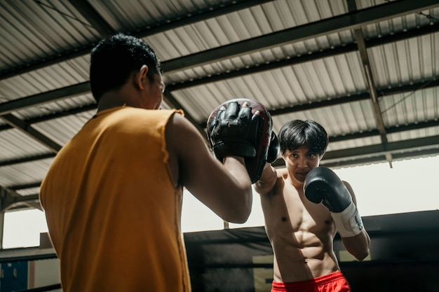 Young man boxer doing exercise hitting punching competing with his trainer at boxing camp