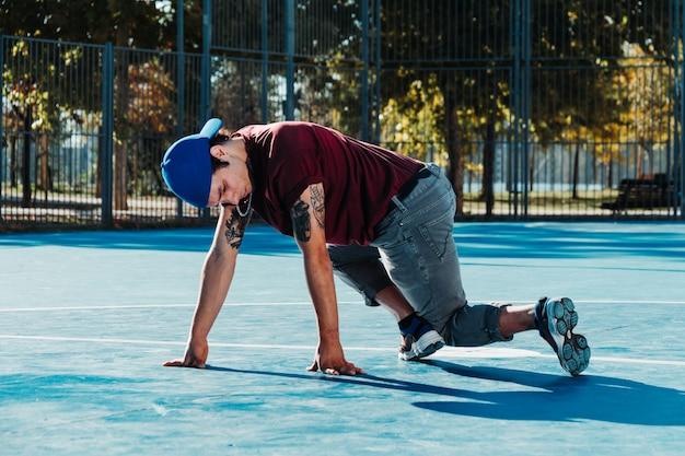 Молодой человек брейк-данс на баскетбольной площадке