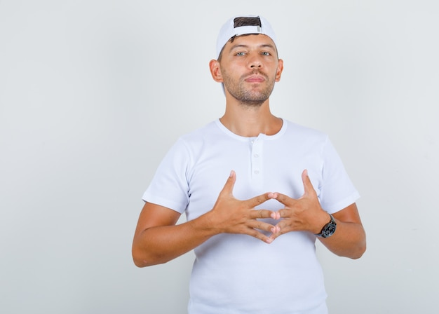 Young man bringing fingers together in white t-shirt, cap and looking proud, front view.