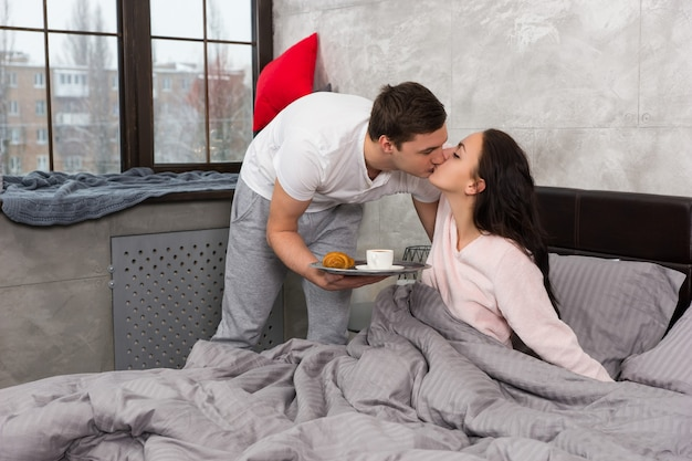 Young man brought breakfast in bed and kissed his happy girlfriend while she sitting in the bed wearing pajama in the bedroom in loft style