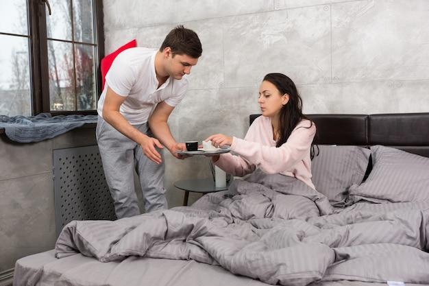 젊은 남자는 침대에서 커피를 가져왔고 그의 여자 친구는 로프트 스타일의 침실에서 잠옷을 입고 침대에 앉아 있었다
