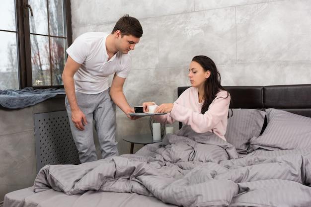 젊은 남자는 로프트 스타일의 침실에서 잠옷을 입고 침대에 앉아 있는 동안 그의 아내가 침대에 커피를 가져왔다