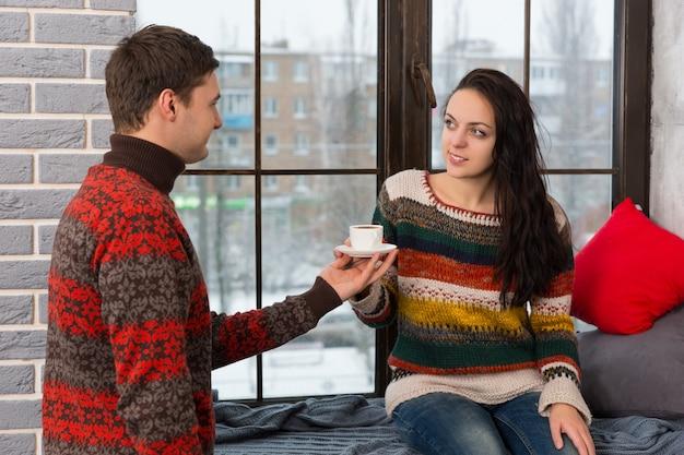 젊은 남자는 여자 친구가 거실에서 베개와 담요를 들고 창턱에 앉아 있는 동안 커피를 가져왔다