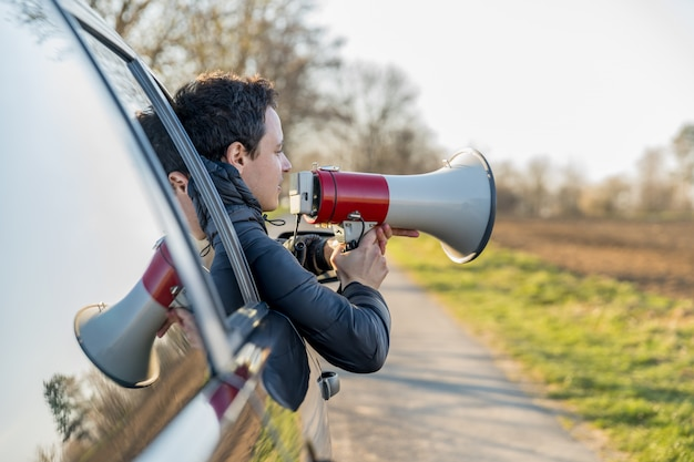 A young man brought into megaphone important news through a car window