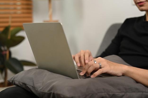 Молодой человек в интернете с ноутбуком на софе.