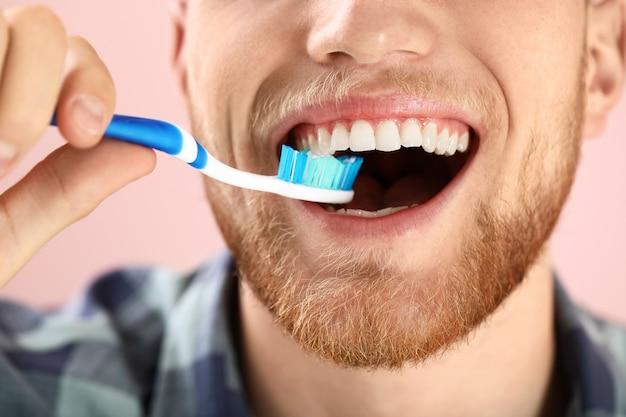 色に歯を磨く若い男