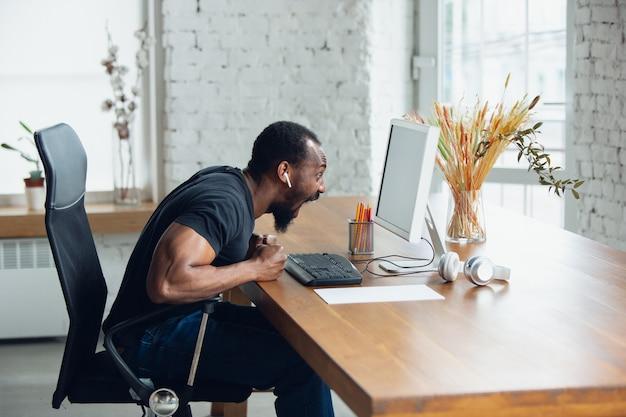 空白の黒いコンピューター画面モニターを探して自宅で若い男の実業家
