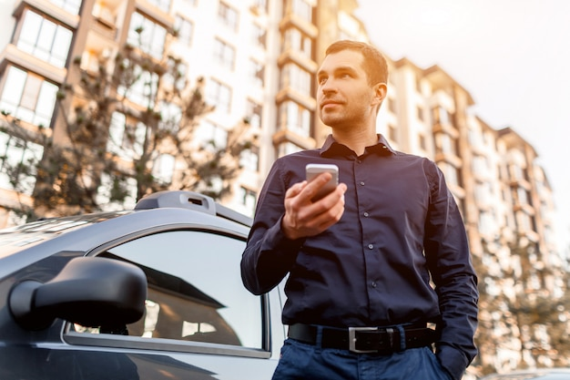 A young man or businessman in a dark shirt stands on the street near the car, looks into the distance in a residential area of the city.