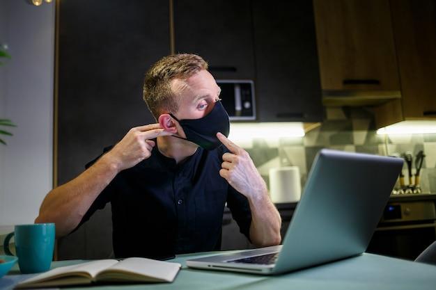 검은색 바이러스 백신 보호 마스크를 쓴 젊은 사업가가 집에서 일하고 노트북으로 식탁에 앉아 있습니다. 검역소에서 집에서 일하기