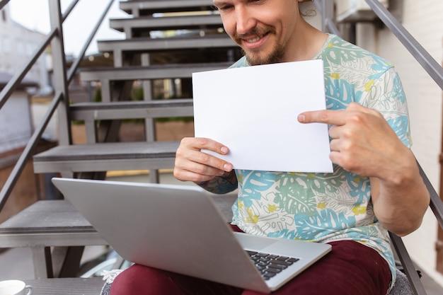 若い男、屋外でラップトップを使用して仕事を探しているビジネスマン、