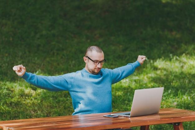 カジュアルな青いシャツを着た若い男性のビジネスマンや学生、リラックスしたメガネ、ラップトップでテーブルに座って、都市公園で携帯電話を伸ばして、手を広げて、屋外で作業します。モバイルオフィスのコンセプト。