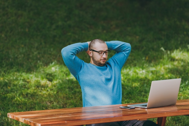 Young man businessman or student in casual blue shirt, glasses relaxing, sitting at table with laptop, mobile phone in city park holding hands behind head, working outdoors. mobile office concept.