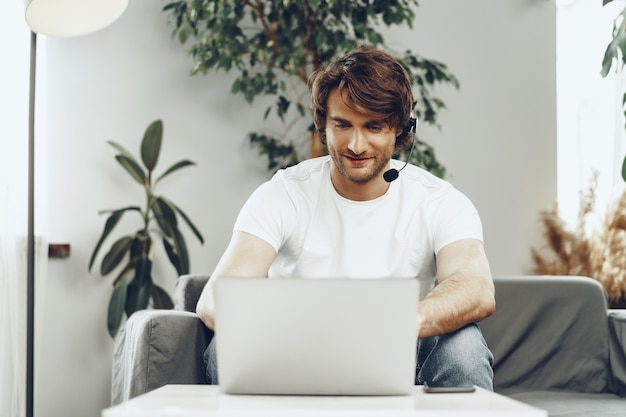 Young man businessman with headset working on laptop from home