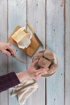 Молодой человек намазывает маслом булочку на старом деревенском столе.
