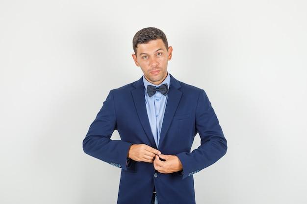 Молодой человек застегивает пиджак в костюме и выглядит уверенно.