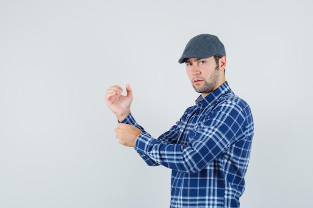 젊은 남자 셔츠, 모자 및 잠겨있는 찾고 그의 셔츠의 소매 단추. 전면보기.
