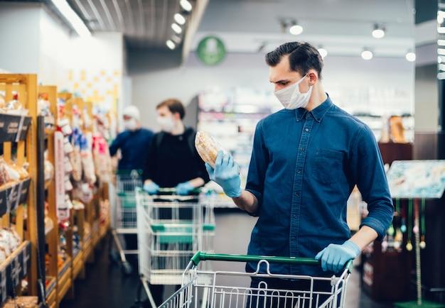 Молодой человек покупает хлеб в супермаркете