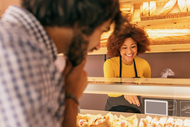Young man buying something in a bakery, is being attended by an pretty afro woman.