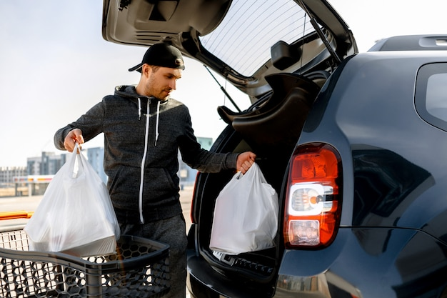 Young man buys food for a week in a large shopping center