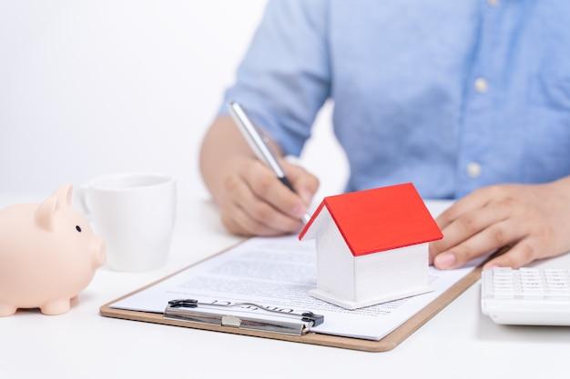 若い男が計算し、家を購入する契約に署名します