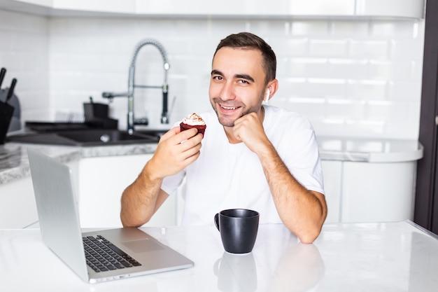 아침에 집에서 랩톱 컴퓨터에서 작업하는 동안 airpods를 통해 휴대 전화로 전화하는 젊은 남자가 케이크를 먹고
