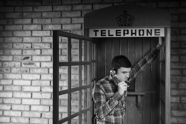 벽돌 벽 배경으로 전화 부스에서 누군가를 호출하는 젊은 남자. 모노크롬으로 촬영했습니다.