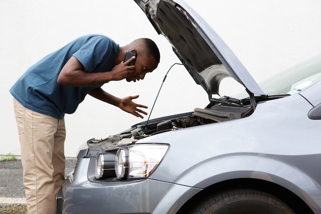 Young man calls for help with a stalled car