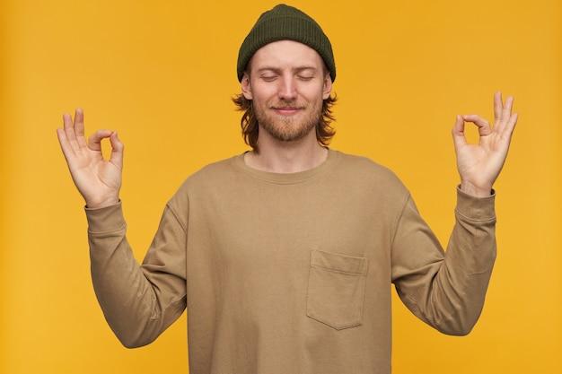Молодой человек, спокойный на вид парень со светлыми волосами, бородой и усами. в зеленой шапке и бежевом свитере. мирно медитирует с закрытыми глазами. стенд изолирован над желтой стеной
